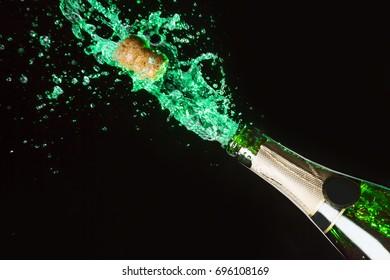 Celebration alcohol theme with explosion of splashing green absinth on black background