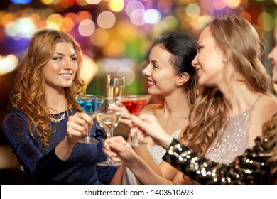 celebration, bachelorette party and holidays concept - happy women or female friends clinking glasses at night club