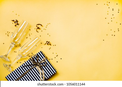 Celebration background - top view of two chrystal champagne glasses, a gift box wrapped in black and white striped paper, ribbons and star shaped golden confetti over yellow background. Copy space.