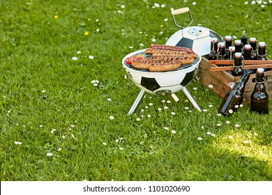 Celebration barbecue Soccer with sausages grilling over a ball shaped portable BBQ with a crate full of bottled beer alongside in a meadow