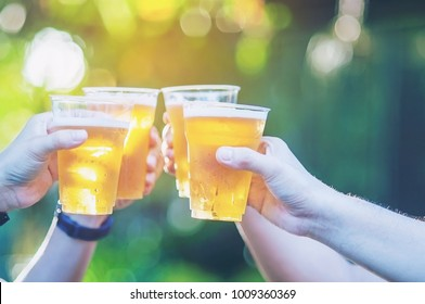 Celebration beer cheers concept - close up hands holding up glasses of beer of people group in outdoor party during their victory competition or successful task meeting