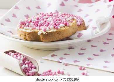 celebration the birth of a daughter with Dutch crispy biscuit with pink sugared aniseed balls, and wooden spoon