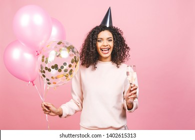 Celebration birthday concept - close up portrait of happy cheerful young beautiful african american woman with pink t-shirt with colorful party balloons and champagne.
