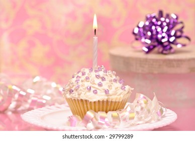 Celebration cake with lit candle and gift in pink background