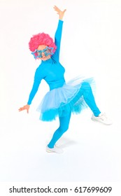 Celebration and children's presentation theme: girl animator in blue suit disco dancer with ballet tutu big funny glasses and pink wig on head on white isolated background in studio