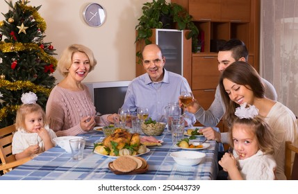 Celebration of christmas in the bosom of family at the table at home