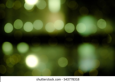 Celebration in the city. Luminous garlands. Soft, colorful bokeh different colors. Fill the entire background. Tender tones yellow, black, brown, green.