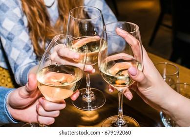 Celebration. Close up people holding glasses of white wine making a toast