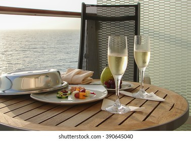 Celebration concept: Champagne with appetizers and fruit on balcony of cruise ship.