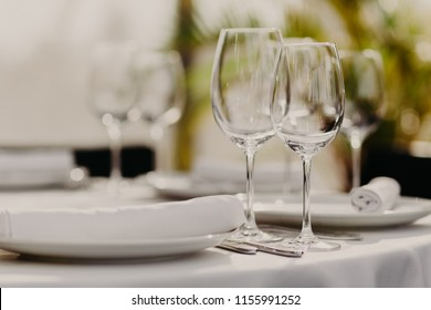 Celebration and dinner concept. Indoor shot of empty wineglasses with empty plates served for guests in restaurant. Festive event. Blurred background.