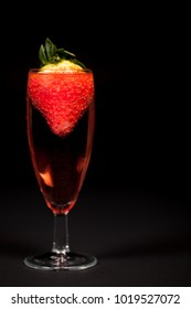 Celebration drink. Pink Champagne sparkling wine with strawberry. Rose bubbly alcoholic drink in glass against black background with copy space.