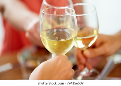 celebration, eating and holidays concept - close up of hands clinking wine glasses