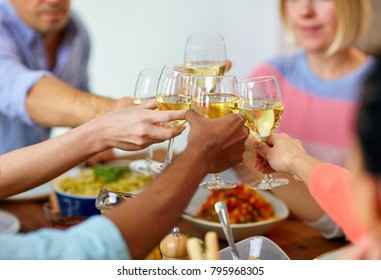 celebration, eating and holidays concept - hands clinking wine glasses