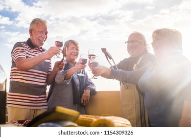 celebration event outdoor for a group of adult people. drkinking wine in the rooftop terrace with nice view on the background. happy lifestyle together men and women cheerful mature. happy lifestyle