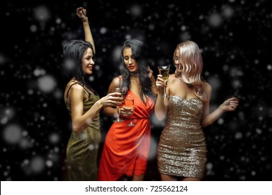 Celebration, friends, new year, christmas and winter holidays concept - happy women with glasses of champagne at bachelorette party at night club over snow