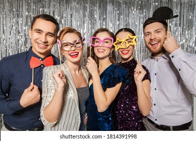 celebration, fun and holiday concept - happy friends posing with party props