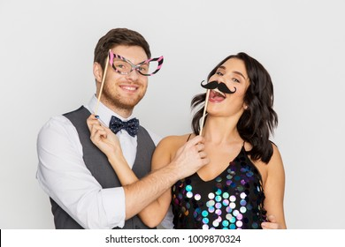 celebration, fun and holidays concept - happy couple posing with party props