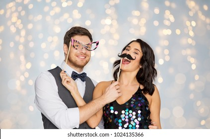 celebration, fun and holidays concept - happy couple posing with party props over festive lights background