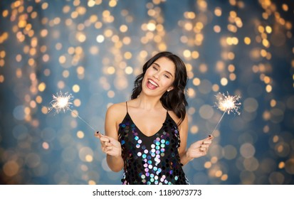 celebration, fun and holidays concept - happy young woman in sequin dress with sparklers at party over festive lights background