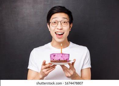 Celebration, holiday and birthday concept. Close-up portrait of amazed and happy young asian man holding b-day cake and smiling amused, throw party, blow out candle for making wish