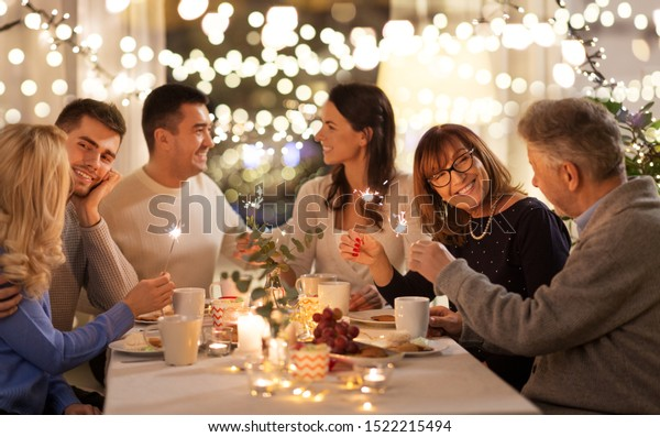 celebration, holidays and christmas concept - happy family with sparklers having fun at dinner party at home