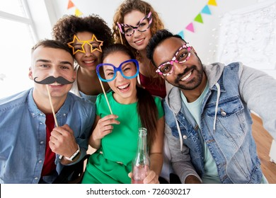celebration and holidays concept - happy friends with party accessories and non-alcoholic drink having fun at home