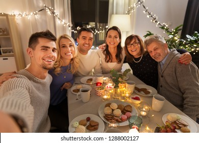 celebration, holidays and people concept - happy family having tea party at home and taking selfie