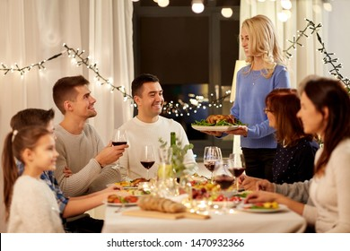 celebration, holidays and people concept - happy woman offering roast chicken to family having dinner party at home