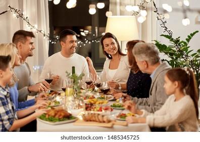 祝祭日と人々のコンセプト – 家庭での夕食会を楽しむ家族