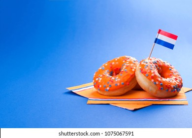 Celebration of the King's Day in the Netherlands. Fun holidays. Orange sweet donats on a blue background and flags. Free space for text. Sivol holiday. Horizontal photo
