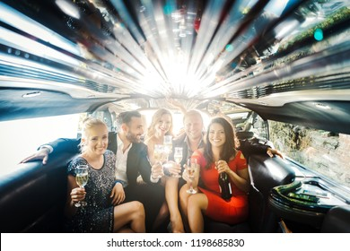Celebration in a limo, woman and men drinking champagne and having a party