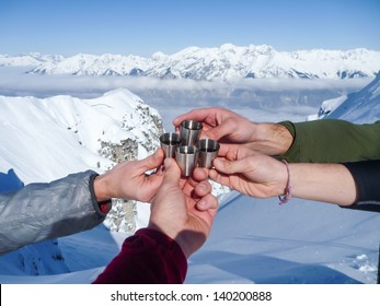 Celebration in mountains.  Shots of spirits at the top of mountain summit during ski tour in the Alps.