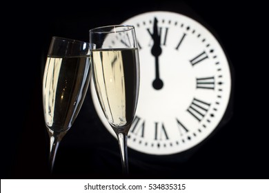 CELEBRATION OF THE NEW YEAR, glasses raising with champagne, background of the clock unfocussed