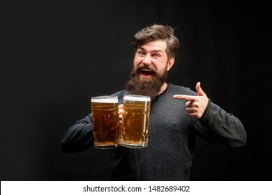 Celebration oktoberfest festival concept. Bearded man holds mug of craft beer pointing with finger to mug. Man in beer pub. Happy brewer. Brewery concept. Happy smiling man with beer. Enjoy in pub.