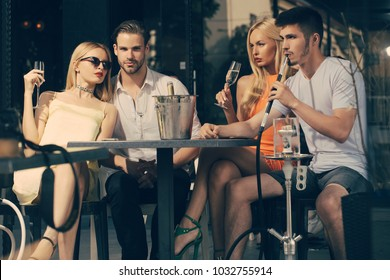 Celebration, party concept. Friends vapor hookah and drink alcohol in bar lounge. Addiction, bad habits. twins women and men relax in shisha cafe outdoor. twins