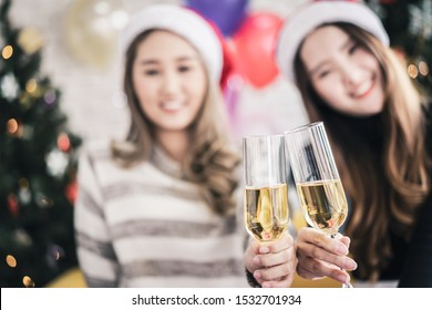Celebration party group of Asian cheerful attractive young woman in Santa Claus hat holding champagne glass happy and funny concept. In 2020 New year holiday. Selective focus.