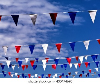 Celebration pennants against spring sky; colored bunting flying against spring or summer sky