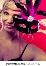 Celebration people concept. Amazing woman with carnival mask. Beautiful female with black dress on red background.