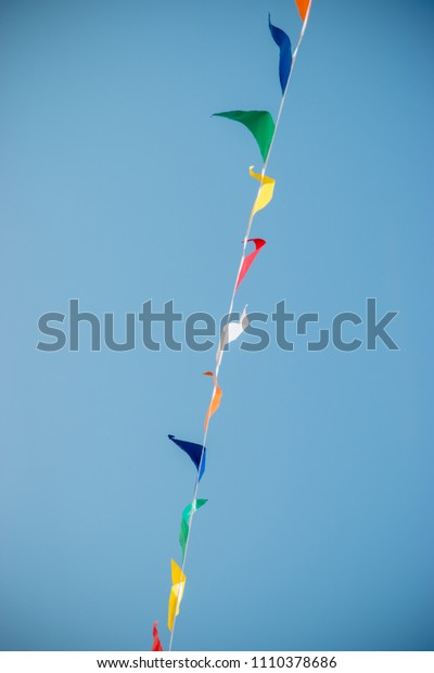A celebration with rows of flags blowing in the wind upwards