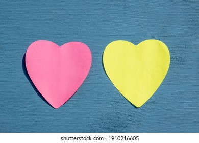 Celebration and special event concept: View from above on one pink and one yellow, empty heart shaped paper stickers on wooden blue background with copy space. For lovers and Valentines day