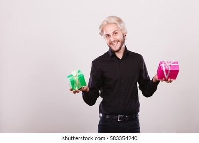 Celebration, special occasion, holidays concept. Trendy young man holding presents pink and green gift boxes in hands