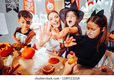 Celebration table. Beaming mother and children with painted faces feeling happy preparing celebration table for Halloween