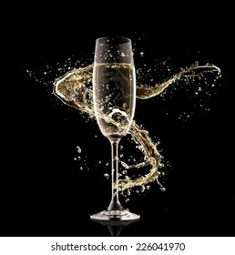 Celebration theme. Glass of champagne with splash, isolated on black background