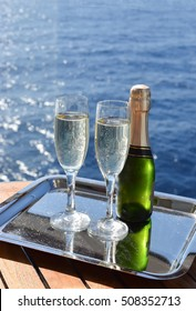 Celebration theme: Two glasses filled with sparkling champagne and small bottle on silver tray. Ocean in background.
