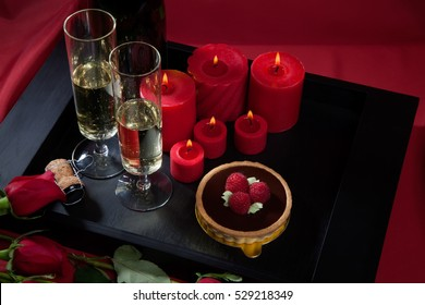 Celebration tray for Valentines Day - Champagne, chocolate raspberry cake, candles, and red roses.