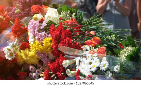 Celebration of Victory Day. Close up many flowers near the memorial of memory. Patriotic holiday of the end of the War.