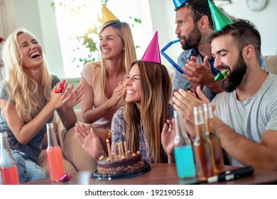 Celebration,friends, party and birthday concept - smiling women blows candles on her birthday cake.
