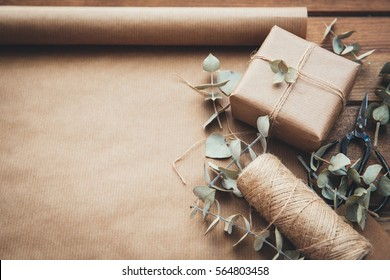 Celebratory concept - set with handmade present box decorated with dry flowers, wrapping tools, packing paper on wooden background. Copy space. Top view