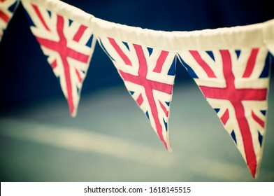 Celebratory vintage British Union Jack flag bunting hanging outdoors in preparation for a street party - Shutterstock ID 1618145515