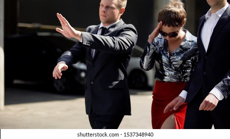 Celebrity bodyguards protecting actress from annoying photojournalist outdoors